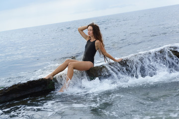 A beautiful slender long-haired girl in a black swimsuit sits on a stone on the sea on a cloudy summer day