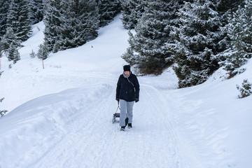 Frau wandert mit Schlitten im Schnee