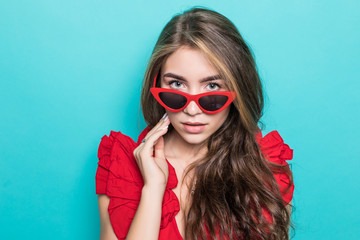 Young beauty woman with sunglasses on a blue background