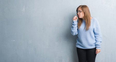 Young adult woman over grey grunge wall wearing glasses feeling unwell and coughing as symptom for cold or bronchitis. Healthcare concept.