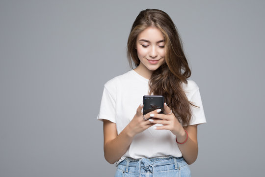Smiling lovely young woman standing and using phone over grey background