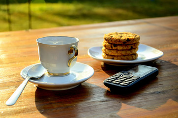 Morning espresso with oatmeal cookies, telephone, teaspoon, saucer, outdoors.
