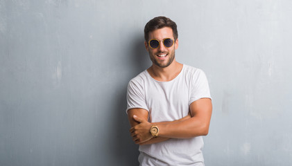 Handsome young man over grey grunge wall wearing sunglasses happy face smiling with crossed arms looking at the camera. Positive person. Wall mural
