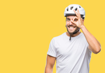 Young handsome man wearing cyclist safety helmet over isolated background doing ok gesture with hand smiling, eye looking through fingers with happy face.