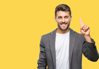 Young handsome business man over isolated background showing and pointing up with finger number one while smiling confident and happy.