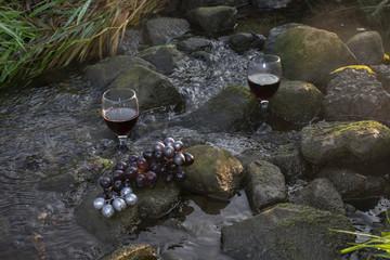Rotweingläser und roten Weintrauben auf Steinen im fließenden Gewässer.