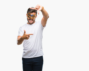 Young handsome man wearing carnival mask over isolated background smiling making frame with hands and fingers with happy face. Creativity and photography concept.