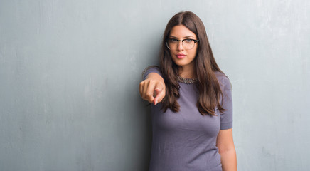 Young brunette woman over grunge grey wall wearing glasses pointing with finger to the camera and to you, hand sign, positive and confident gesture from the front