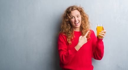 Young redhead woman over grey grunge wall drinking a glass of orange juice very happy pointing with hand and finger