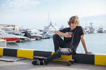 stylish young blond curly hair man sitting on longboard and using smartphone and smile