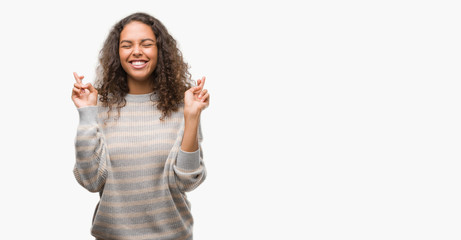Beautiful young hispanic woman wearing stripes sweater smiling crossing fingers with hope and eyes closed. Luck and superstitious concept.