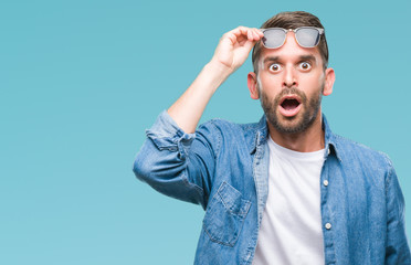 Young handsome man wearing sunglasses over isolated background afraid and shocked with surprise expression, fear and excited face. Wall mural