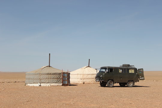 Yurts and former Russian military off-road vehicle in the Gobi desert - Mongolia