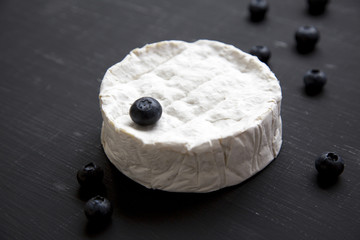 Camembert cheese with blueberries on dark table, side view. Food for wine.