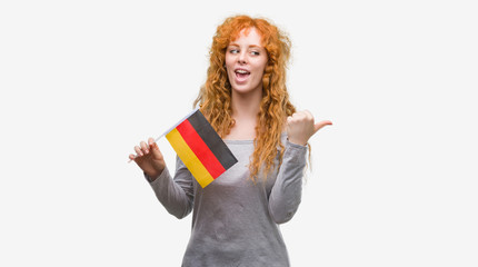 Young redhead woman holding flag of Germany pointing and showing with thumb up to the side with happy face smiling