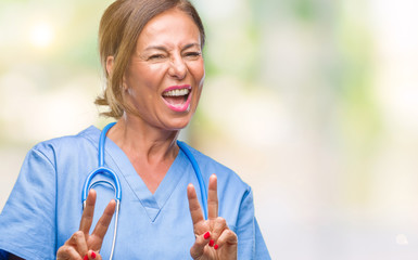 Middle age senior nurse doctor woman over isolated background smiling looking to the camera showing fingers doing victory sign. Number two.