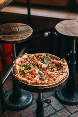Pizza carbonara on rustic wooden table at the restaurant. Food photography concept. Copyspace