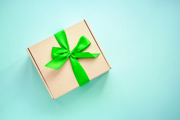 One craft paper box  with green ribbon bow on blue background from above. Minimalism, copy space