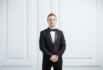 Attractive young man in tuxedo smiling and looking at camera