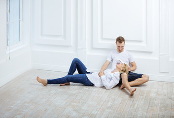 Young couple in casual clothes sitting on floor and talking
