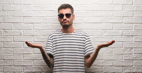 Young adult man wearing sunglasses standing over white brick wall clueless and confused expression with arms and hands raised. Doubt concept.
