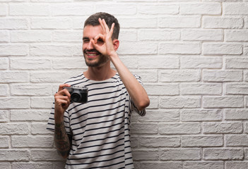 Young man holding vintage camera standing over white brick wall with happy face smiling doing ok sign with hand on eye looking through fingers