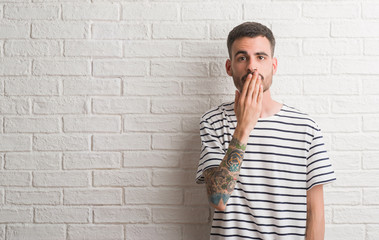 Young adult man standing over white brick wall cover mouth with hand shocked with shame for mistake, expression of fear, scared in silence, secret concept