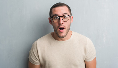 Young caucasian man over grey grunge wall scared in shock with a surprise face, afraid and excited with fear expression
