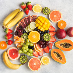 Wall Mural - Raw fruits berries platter, mango, oranges, kiwi strawberries, blueberries grapefruit grapes, bananas apples on the white plate, on the off white table, top view, square, selective focus