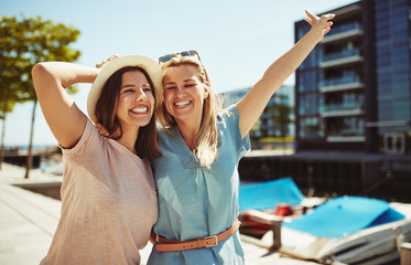 Two laughing female friends having fun walking together in summe