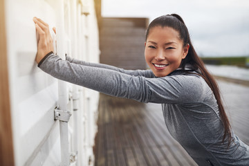 Smiling young Asian woman stretching outdoors before a run
