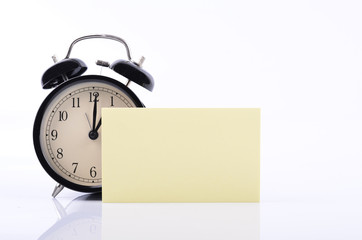 Listing memo and schedule concept,vintage alarm clock and yellow sticky notepad with copy space for  text on table