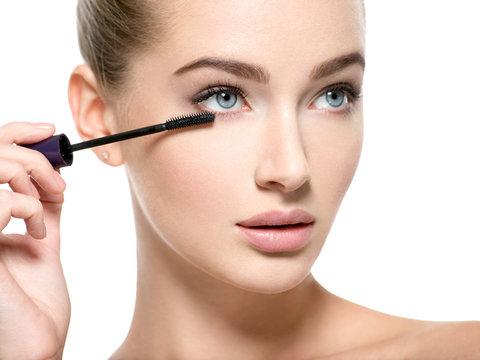 Girl makes makeup. Woman apply mascara on eyelashes
