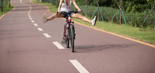 Free woman cyclist riding bike in spring tropical park