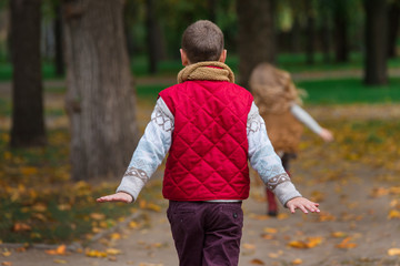 Happy children play and run in autumn park. No face