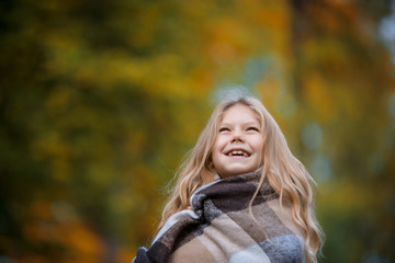 Portrarait of positive little girl covered in plaid in the autumn park
