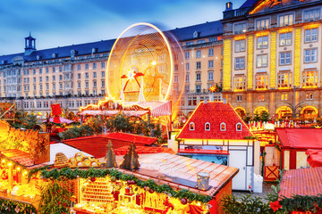 Traditional European Christmas Market in Dresden, Germany, Saxony. View on amusement park - the rolling ferry wheel on long exposure. Festive xmas decorated and illuminated market.