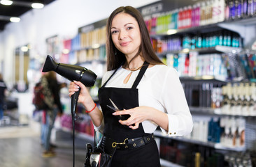 Female hairdresser in apron  holding blow dryer and hair cutters in shop