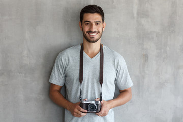 Smiling handsome male photographer in t shirt, holding retro film photo camera, standing against gray textured wall