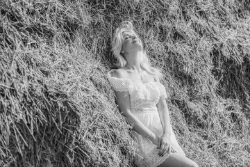 Nature time vacation and people concept - young woman dreaming on cereal field. . Beauty romantic girl outdoors against hay stack. Photo of sexy blonde in a field with haystacks