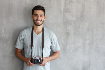 Portrait of smiling handsome male photographer in gray t shirt, holding his camera, standing against gray textured wall with copy space for your ads
