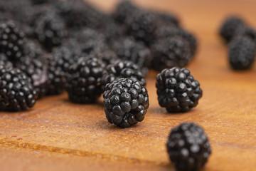 Ripe blackberries on a wooden table. Macro image.