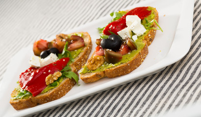 Toasts with guacamole, fresh vegetables, feta cheese