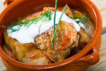 Tasty cabbage rolls in leaves of cabbage  in clay pot with sour cream