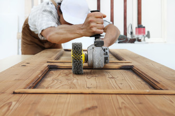 carpenter work the wood with the sander grinding electric tools for rustic wooden effects