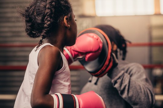 Rear view of a boxing kid practicing her punches