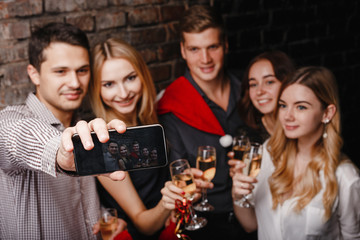 New Year, event, party, holiday, fun. Company of cheerful friends in Santa caps celebrating, making selfie on smart phone, drinking champagne