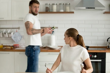 Mad funny girlfriend look dissatisfied scold boyfriend for bad dinner or breakfast, surprised man frustrated by wife food complaint, man cook dish at home kitchen. Concept of feminism, gender equality
