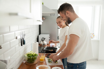 Happy young couple cooking breakfast in modern kitchen together, smiling wife making omelette or scrambles eggs, husband slice vegetables, lovers prepare food spending morning at home