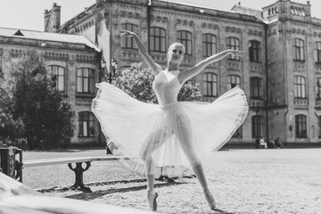 Ballerina dancing on the street.Young beautiful ballerina in dress and pointe shoes dancing outdoors. Ballerina posing in the center of Europe
